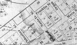 """Figure 1. The Mills Plat of 1859. This close-up of the Mills Plat of 1859 shows the location of the Campo Santo in Block 28. Due to damage to the map, the """"Campo"""" is partially rubbed out; only """"Santo"""" can be read clearly. Just above the cemetery name is the image of a monument and the words """"Dr. Giddings Monument."""" Courtesy of the El Paso County Historical Society."""